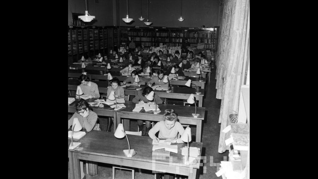 Studenci podczas sesji egzaminacyjnej w czytelni Biblioteki Uniwersyteckiej, lata 70. ub. wieku.